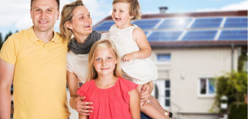 Happy Family Standing Together Outside The House With Solar Panel Fitted On Roof
